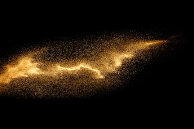 Abstrakte sandwolke goldfarbiges sandspritzen gegen dunklen hintergrund gelbe sandfliegenwelle in der luft.