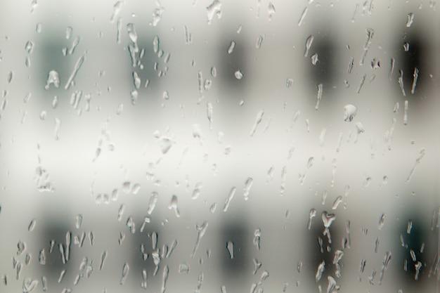 Abstrakte textur von wassertropfen am fenster. glänzende wassertropfen auf einer transparenten oberfläche. regentropfen auf der glasoberfläche.