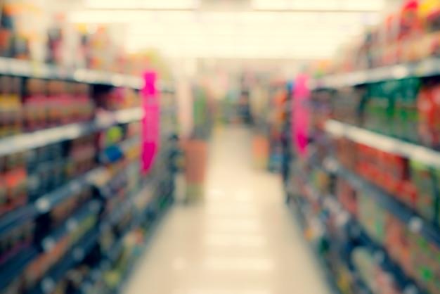 Abstrakte unschärfe des produktanzeigenregals im supermarkthintergrund.