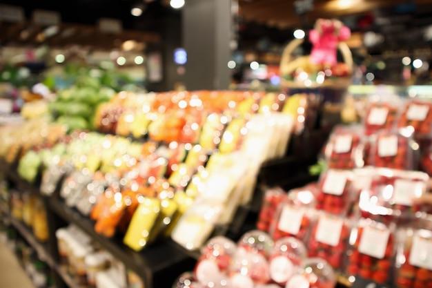 Abstrakte unschärfe organisches frisches obst und gemüse auf lebensmittelregalen im defokussierten bokeh-lichthintergrund des supermarktgeschäfts defokussiert
