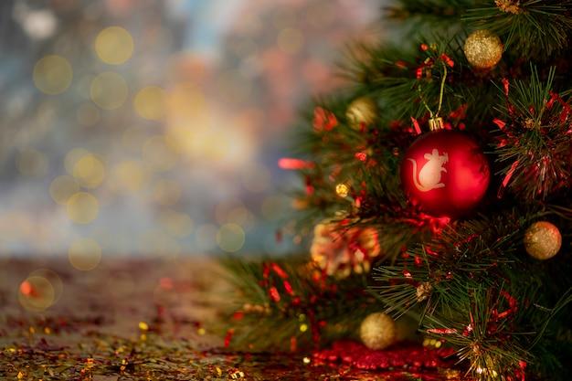 Abstrakte unschärfe. roter weihnachtsball mit simbol des neuen jahres auf einem baum bokeh hintergrund.