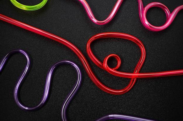 Abstrakte vollfarbige plastiklinie auf dunklem hintergrund