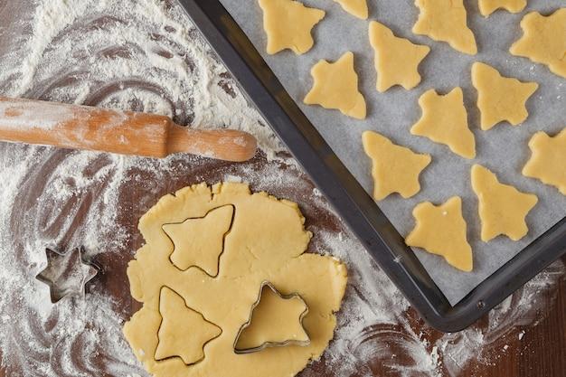 Abstrakte weihnachtsnahrung mit plätzchenformen und mehl