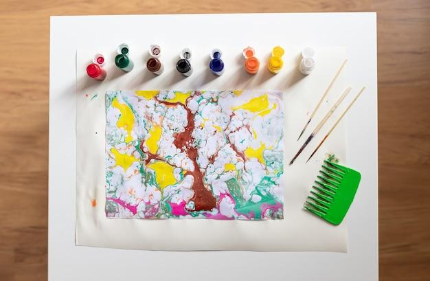 Abstrakte zeichnung ebru und satz von werkzeugen auf tabelle
