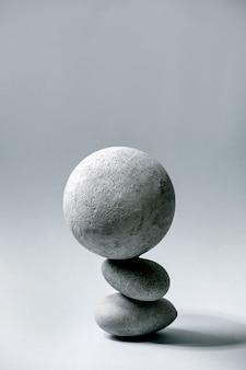 Abstrakte zusammensetzung der kugel und der steine des ausgeglichenen grauen geometrischen objekts. speicherplatz kopieren. modernes konzept zur produktpräsentation.