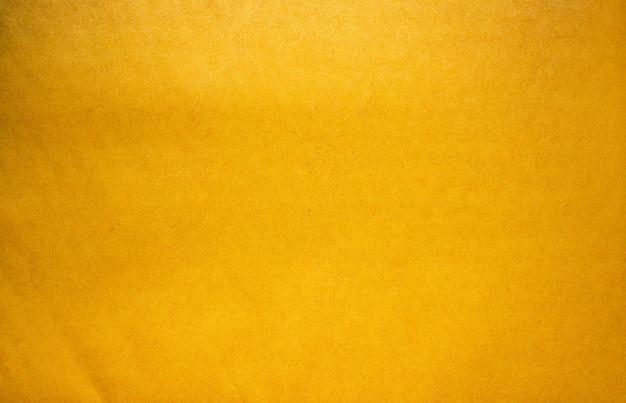 Abstrakter alter gelber papierbeschaffenheitshintergrund