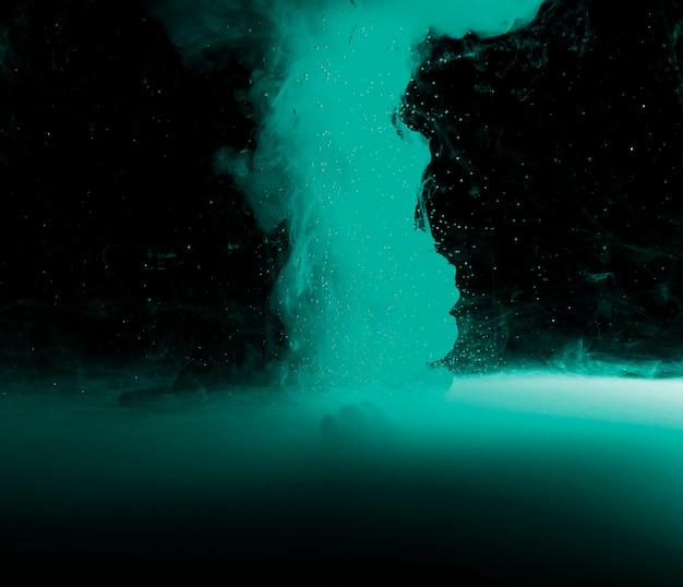 Abstrakter azurblauer nebel und stückchen in der dunkelheit
