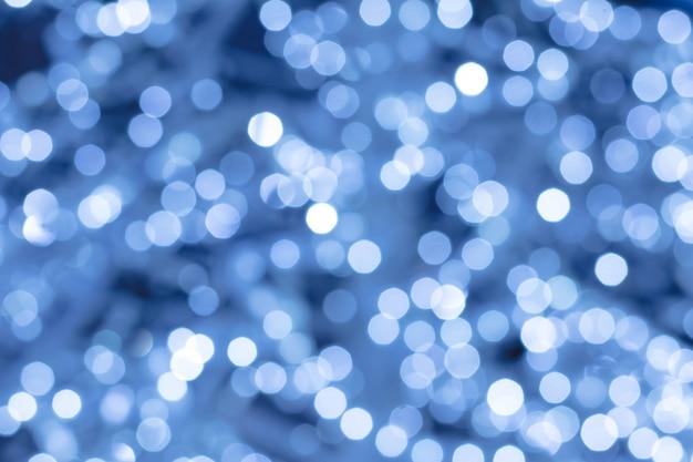 Abstrakter blauer hintergrund mit nachtlichtern, bokeh. verschwommener hintergrund, defokussierte glänzende kreise.