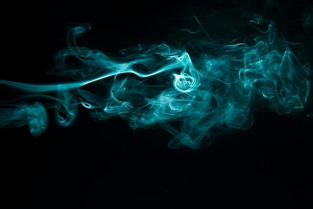 Abstrakter blauer rauch verschiebt sich auf schwarzen hintergrund
