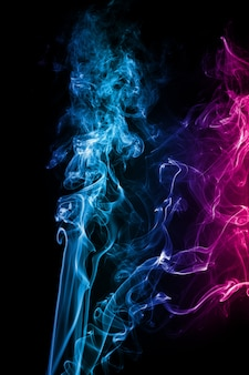 Abstrakter blauer rosa farbiger rauch floss auf schwarzen hintergrund.