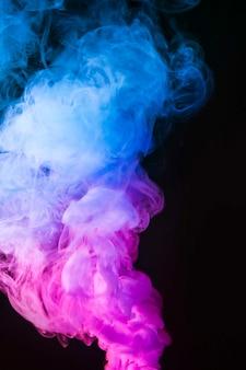 Abstrakter blauer und rosa rauch verschieben sich auf schwarzen farbhintergrund