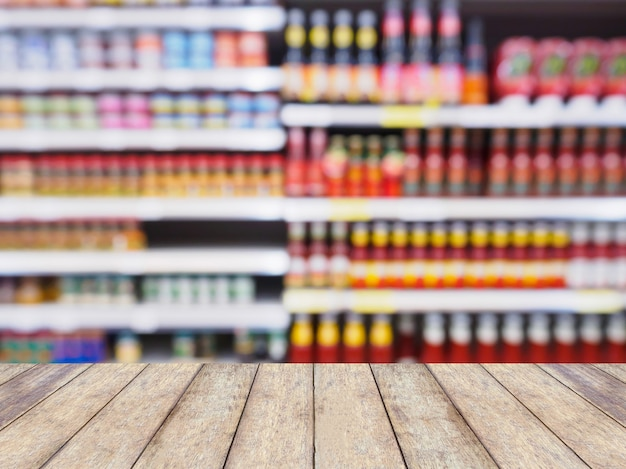 Abstrakter defokussierter unschärfehintergrund des supermarktes mit holztisch