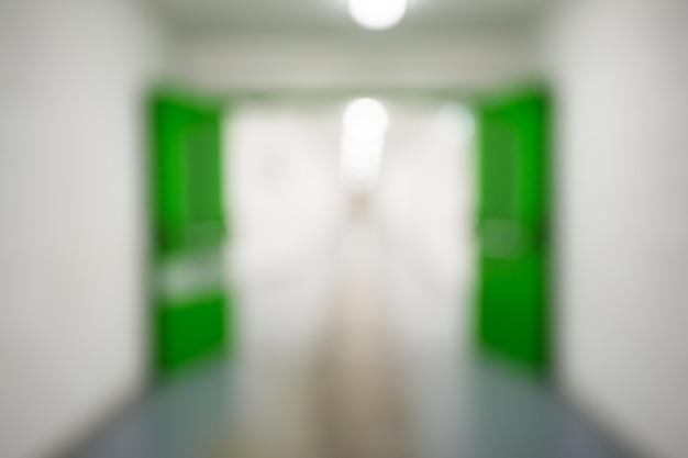 Abstrakter defokussierter unscharfer hintergrund, leerer fabrik- oder pflanzenkorridor oder einkaufszentrum oder dienstkorridor mit grünen türen