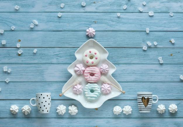 Abstrakter dekorativer weihnachtshintergrund mit süßigkeiten, kaffeetassen, marshmallows, donuts und zuckerkristallen. platte in weihnachtsbaumform und süßigkeiten angeordnet auf rustikalem blauem hölzernem hintergrund.