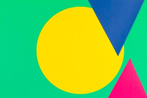 Abstrakter farbpapier-texturhintergrund mit bunter runder kreisdreieckformgeometriezusammensetzung auf hellgrün