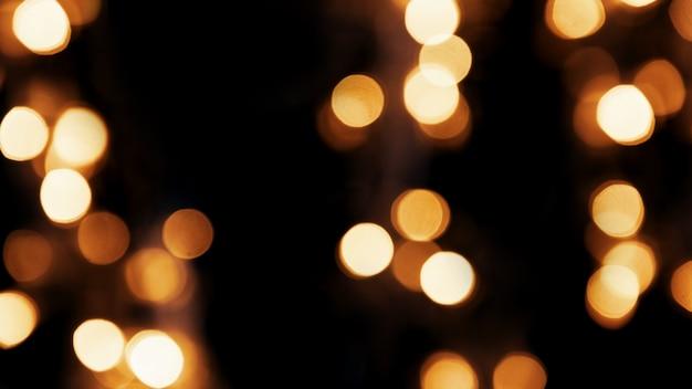 Abstrakter feiertagshintergrund mit den verwischten goldenen lichtern des bokeh auf dem schwarzen hintergrund