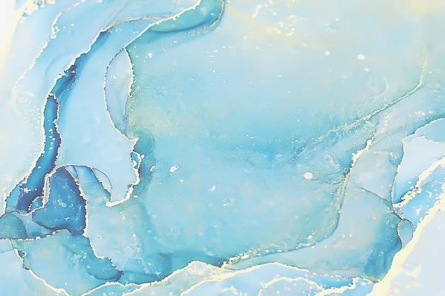 Abstrakter flüssiger tintenmalereihintergrund in pastellfarben mit goldspritzern Premium Fotos