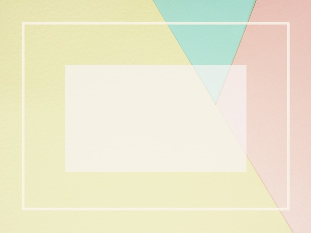 Abstrakter geometrischer farbpapierhintergrund im pastellrosa gelb und blau mit leerem rahmen