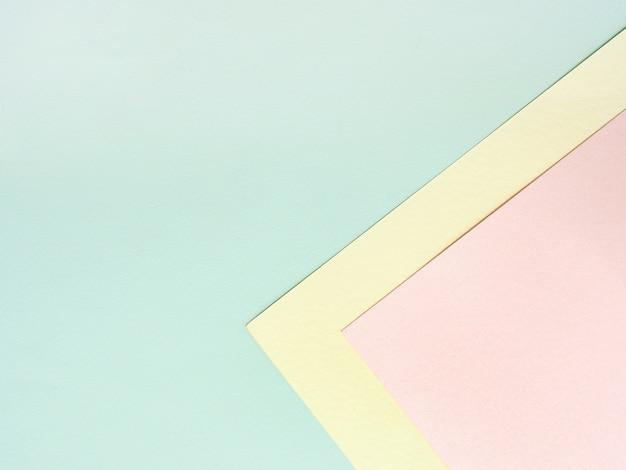 Abstrakter geometrischer farbpapierhintergrund im pastellrosa gelb und blau