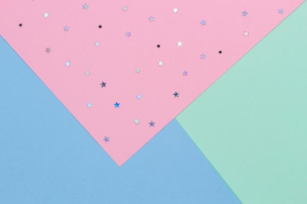 Abstrakter geometrischer festlicher pastellfarbpapierhintergrund mit draufsicht der glitzersterne