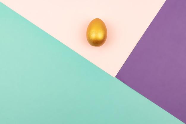 Abstrakter geometrischer papierhintergrund der pastellrosa- und purpurfarben mit goldenem osterei.
