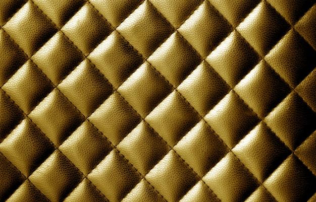 Abstrakter goldlederhintergrund mit textur.