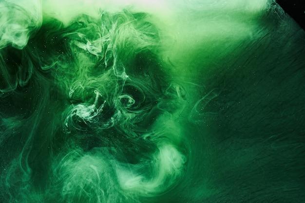 Abstrakter grüner farbhintergrund. wirbelnder lebhafter shisha-rauch, smaragdgrüner unterwasserozean, dynamische farbe im wasser