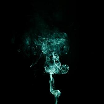 Abstrakter grüner rauch, der auf schwarzen hintergrund wirbelt