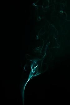 Abstrakter grüner rauch verschiebt sich auf schwarzem hintergrund