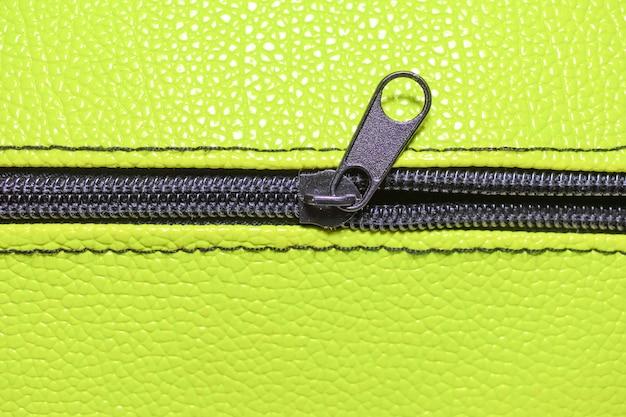 Abstrakter hellgrüner hintergrund, halb geöffneter schwarzer reißverschluss des ledernen geldbeutels