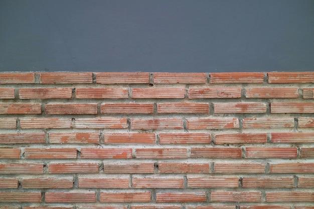 Abstrakter hintergrund, alter ziegelstein mit zementwand.