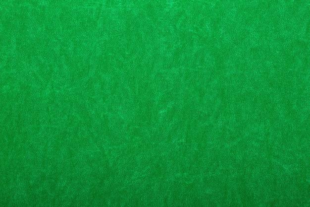 Abstrakter hintergrund aus grünem filz auf casino-tisch