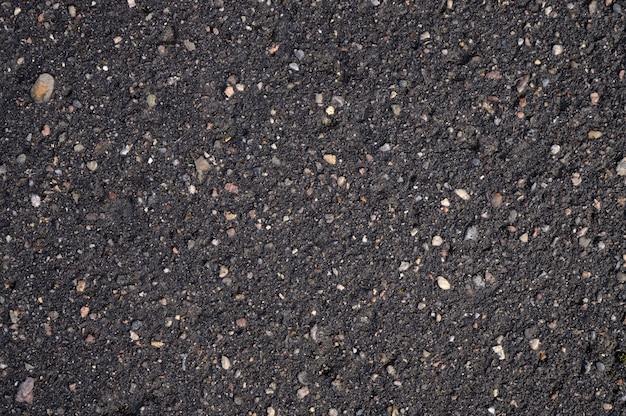 Abstrakter hintergrund aus schwarzem nassem asphalt mit einschlüssen von kieselsteinen