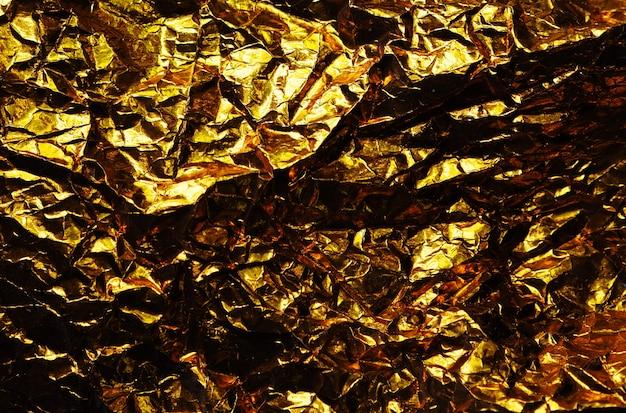 Abstrakter hintergrund der goldfolienplatte