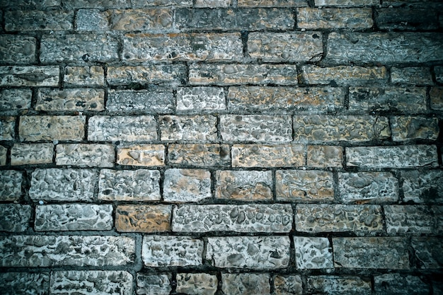 Abstrakter hintergrund des alten kopfsteinpflasters. graue steinziegelpflaster textur. nahaufnahme der alten straße. spaziergang in einer alten stadt. alte ziegelsteinbeschaffenheit. alter straßenbau.