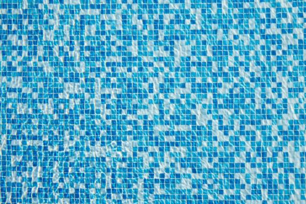 Abstrakter hintergrund des funkelnden kühlen blauen wassers in einem mosaik-schwimmbad