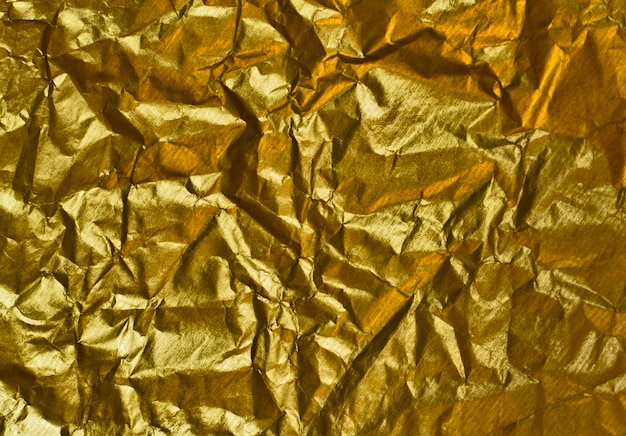 Abstrakter hintergrund des geknitterten goldenen papiers