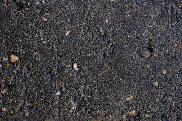 Abstrakter hintergrund des schwarzen nassen asphalts mit einschlüssen von kieselsteinen
