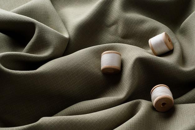 Abstrakter hintergrund, gebogener dunkler schöner stoff und spule mit weißen fäden, kopienraum. nähen des minimalismus-konzepts. drapierter grauer stoff liegt in einer schönen welle.