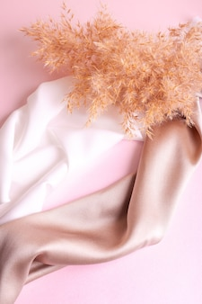 Abstrakter hintergrund in sanften farben von seidenstoffen auf rosafarbenem perlpapier und zweig trockenes beige reed. schöne trendtextur.
