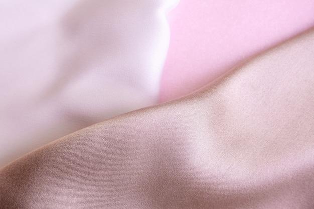 Abstrakter hintergrund in weichen farben von seidenstoffen auf rosafarbenem perlenpapier. schöne trendtextur.