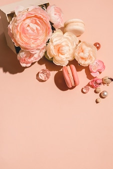 Abstrakter hintergrund mit blumen und einer geschenkbox in gedämpftem schatten. trendy pastell pfirsich monochrom minimales konzept