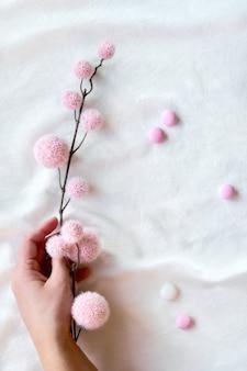 Abstrakter hintergrund mit hand, die dekorativen zweig mit rosa weichen kugeln hält