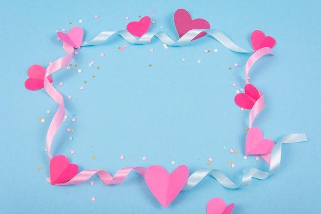 Abstrakter hintergrund mit papierherzen, bänder für valentinstag.