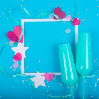 Abstrakter hintergrund mit papierherzen, rahmen, blauen champagnergläsern für valentinstag.