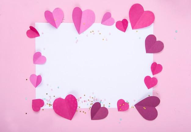 Abstrakter hintergrund mit papierherzen und leerem weißen rahmen für valentinstag.
