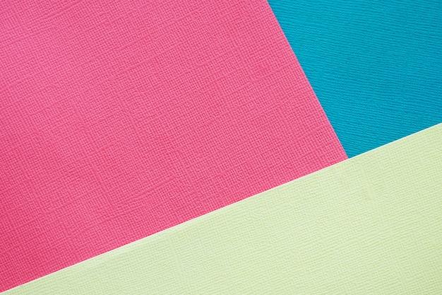 Abstrakter hintergrund und beschaffenheit. drei blätter mehrfarbiges rosa, blaues und hellgelbes strukturpapier.