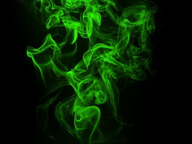 Abstrakter hintergrund und dunkelheitskonzept des grünen rauches