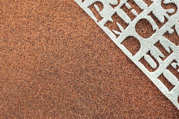 Abstrakter hintergrund und textur braun glänzendes material mit glitzer und glänzendem silbermaterial mit geschnitzten buchstaben.