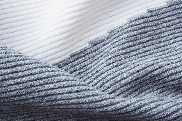 Abstrakter hintergrund und textur grauer und weißer strickstoff achtlos zerknittertes, gestreiftes muster.